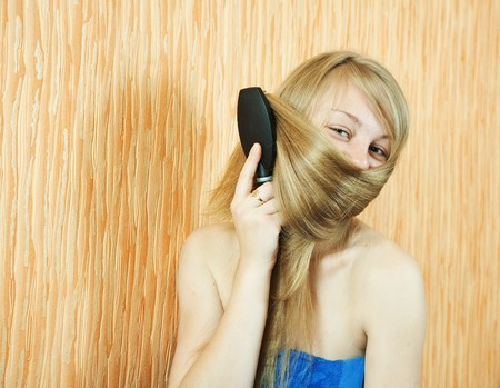 Girl combing her long hair in home interior photo