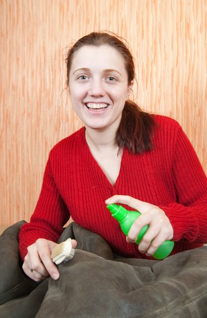 young Woman cleaning a sheepskin with whisk broom at home Stock Photo - 7103838