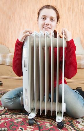 young smiling girl is sitting by a oil heater  Stock Photo
