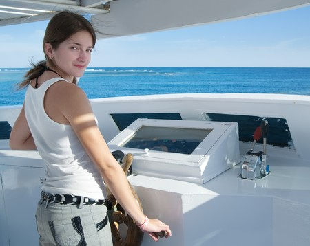 The beautiful young girl with a steering wheel of the yacht photo