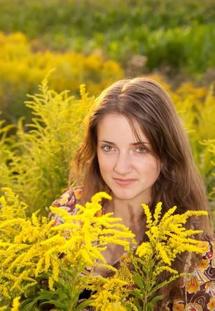langharige tiener meisje in gras tijdens de zons ondergang