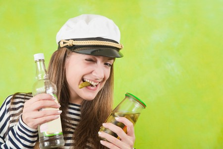 Pretty female sailor with bottle of vodka and pickle over green background photo