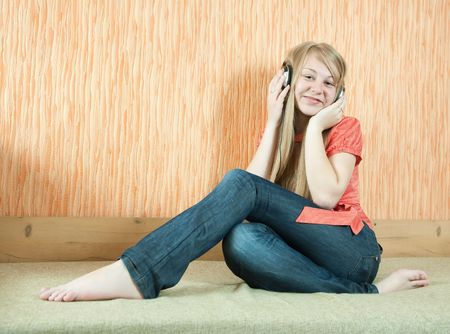 househould: Young beautiful happy woman listening music in headphones