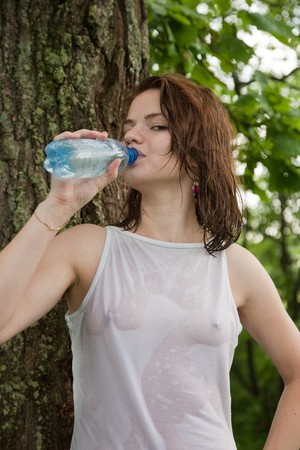 wet jeans: Beautiful girl drinking water near old tree