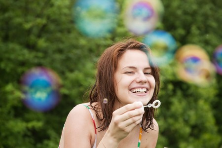 Happy girl making soap bubbles against trees photo