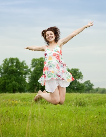 Jumping  pretty brunette  girl  against summer meadow photo
