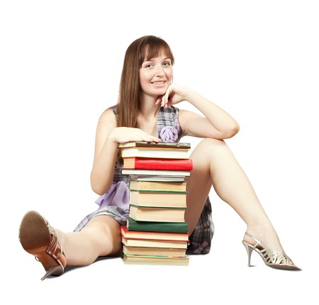sexy schoolgirl: Female student sitting with pile of books, isolated over white Stock Photo