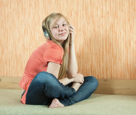 househould: Young   happy woman listening music in headphones on  couch