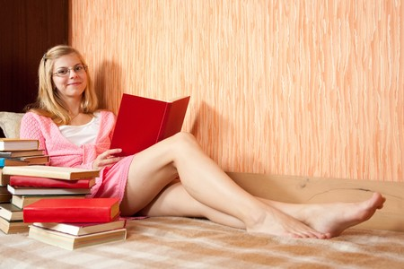young sexy girl reading books on sofa at home photo