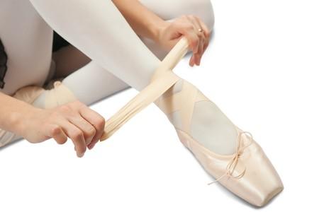dance drama: Closeup of  Ballerina putting on pointes over white  Stock Photo