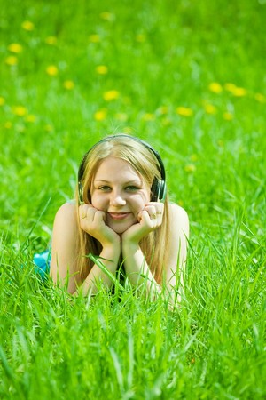 teen girl listening music and lying on grass photo