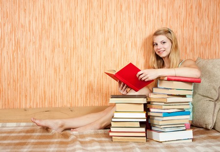 pretty female student reading book on sofa at home photo