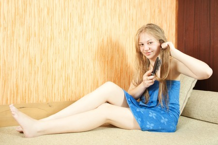 Girl combing her long hair in home inter Stock Photo - 7235922