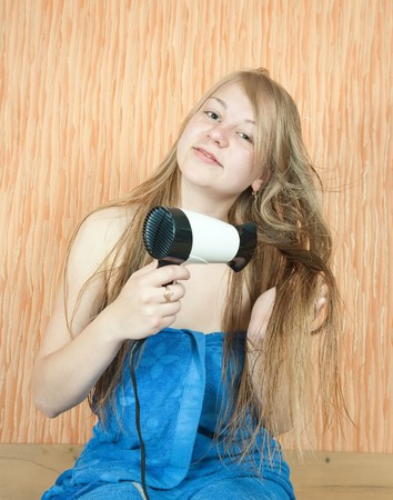 Girl dryes her long hair in home inter Stock Photo - 7235909