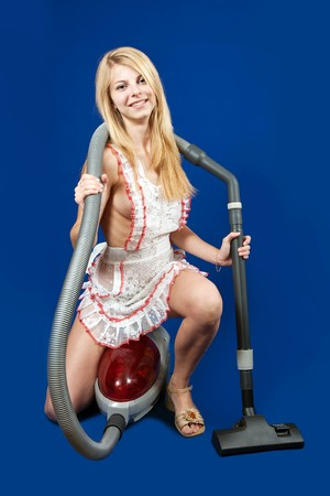 Sexy Woman with vacuum cleaner over blue background photo