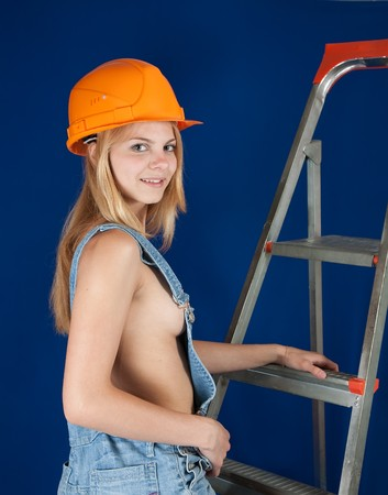 Sexy girl in dungarees and hardhat on stepladder over blue photo