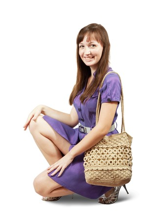 young girl with handbag sitting on white background