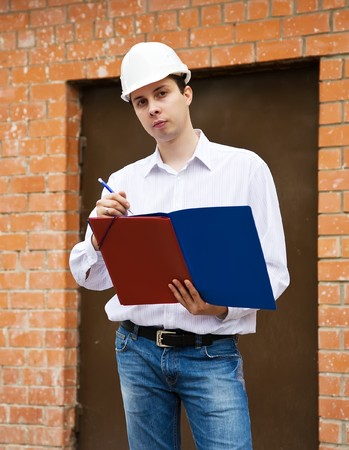 tasker: builder in hard hat  writing against  the brick wall Stock Photo
