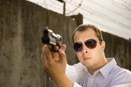 convicted: young man aiming a black gun against the prison wall Stock Photo