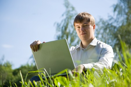 Handsome man  working on laptop in the meadow photo
