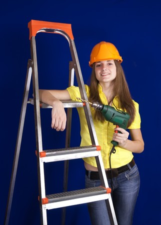 young woman with drill near on scaling-ladder over blue photo