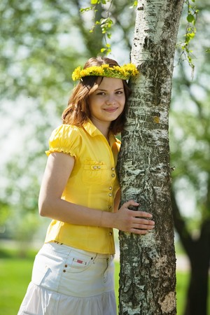 Brunette teen girl in chaplet near birch