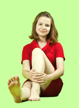 Sitting girl in red dress over green background photo
