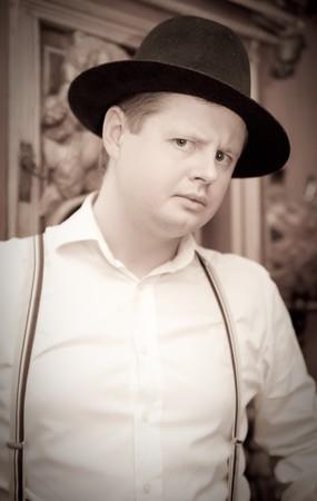 Vintage portrait of man in black fedora hat photo