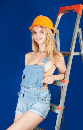 dungarees: Sexy girl in dungarees and hardhat on stepladder over blue