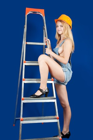 Sexy  female  builder  with  ladder over blue photo
