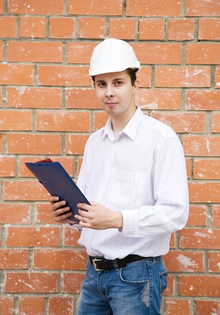 tasker: handsome businessman with documents against  the brick wall Stock Photo