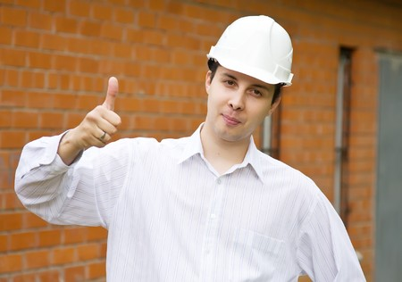 casualy: Happy builder with  thumbs up against  the brick wall Stock Photo