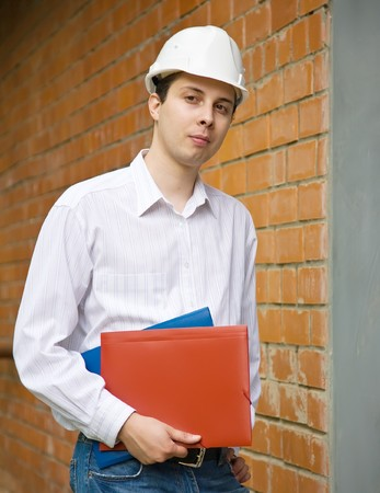 tasker: builder in hardhat with documents  against  the brick wall Stock Photo