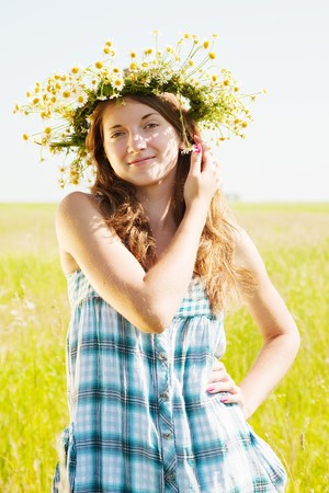 chaplet: long-haired teen girl  in camomiles chaplet against summer field
