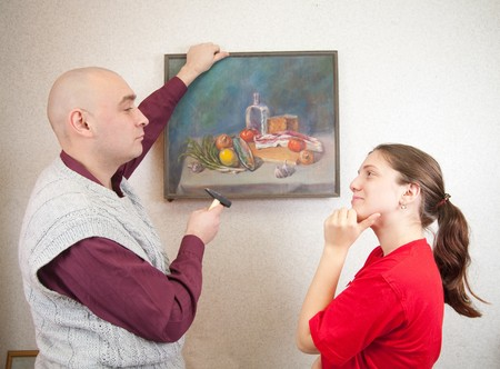 A young and attractive couple hanging up an art picture on their wall photo