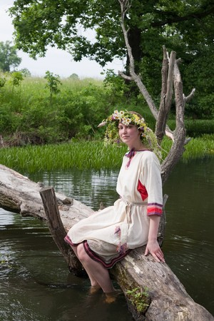 girl  in russian traditional clothes against river photo