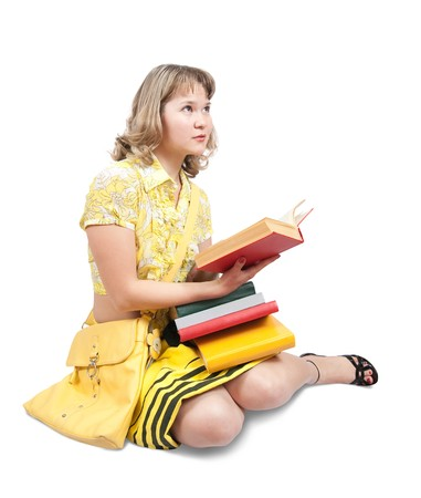 teener: Sitting student dressed in yellow  reading book over white