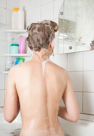 Rear view of girl shampooes in white bathroom photo