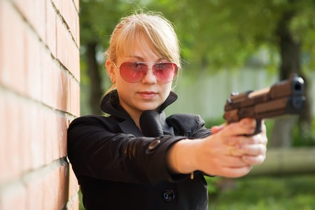 young woman aiming black gun  near  the brick wall photo