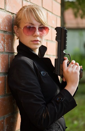 woman with gun against  the brick wall photo