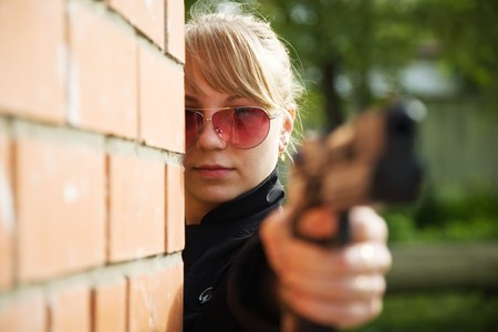 Female model performing glamour secret agent with gun photo