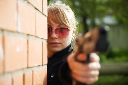 airsoft gun: Female model performing glamour secret agent with gun
