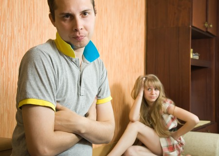 Young sad woman and man at home, selective focus photo
