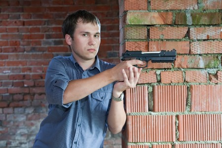 man with gun  against of the brick wall Stock Photo - 7322696