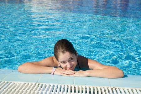 Young woman enjoying a swimming pool at resort hotel photo