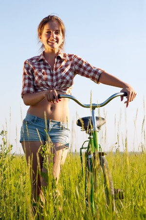 Happy young girl with  bicycle on green meadow photo