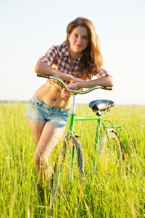 Happy young girl with  bicycle in grass meadow photo