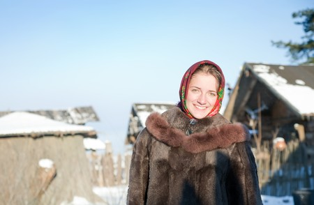 girl in  fur coat against  winter rural landscape photo