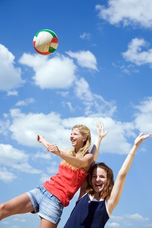 beach volley: Young girls playing volleyball against blue sky Stock Photo