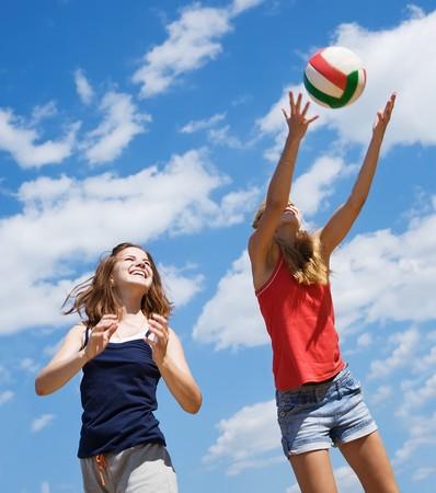 pelota de voley: Muchachas jóvenes jugando voleibol contra el cielo azul  Foto de archivo
